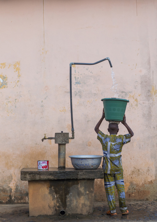 Benin, West Africa, Porto-Novo, child collecting water in the street