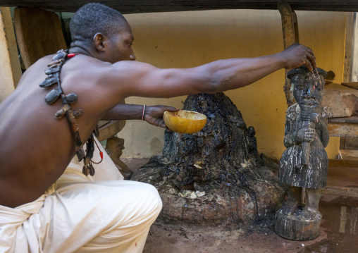 Benin, West Africa, Bonhicon, kagbanon bebe voodoo priest putting some oil on a fetish during a ceremony