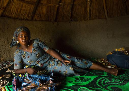 Benin, West Africa, Taneka-Koko, peul bride waiting for her groom lying on her bed inside her hut