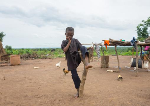 Benin, West Africa, Taneka-Koko, a fulani peul tribe boy resting on a piece of wood