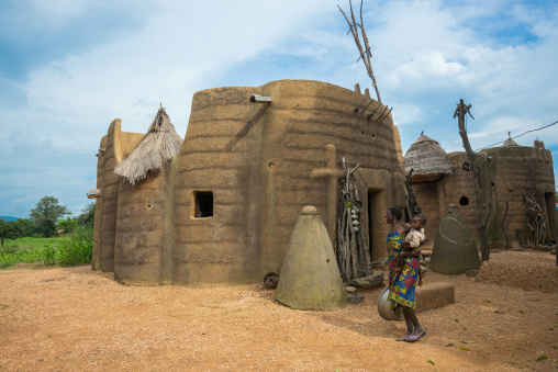 Benin, West Africa, Boukoumbé, mother and her baby in front of her traditional tata somba house with thatched roofs and granaries