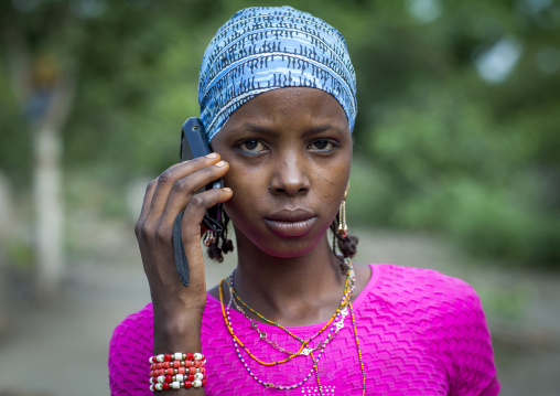 Benin, West Africa, Gossoue, a beautiful tattooed fulani peul tribe woman pausing with her mobile phone