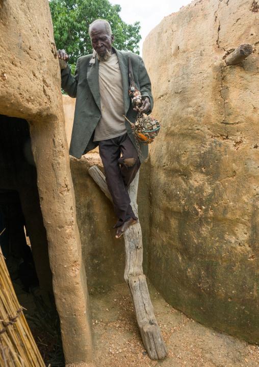 Benin, West Africa, Boukoumbé, man climbing a ladder in a traditional tata somba house