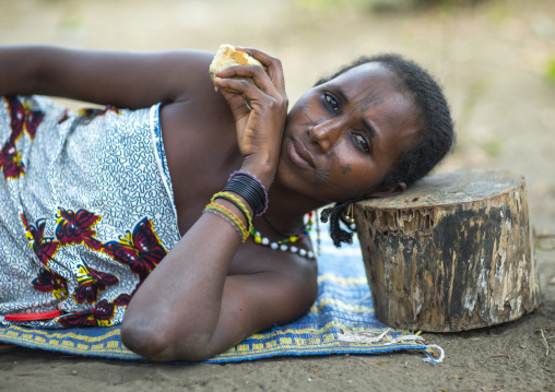 Benin, West Africa, Gossoue, a beautiful tattooed fulani peul tribe woman resting on a piece of wood