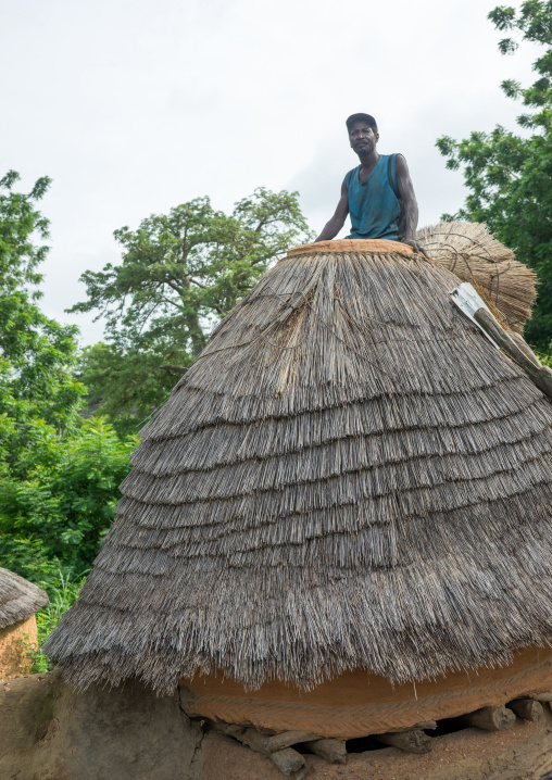 Togo, West Africa, Nadoba, man standing on the roof of a traditional tata somba house