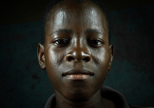 Benin, West Africa, Koussou, a somba tribe teenager with his face covered with linear scars