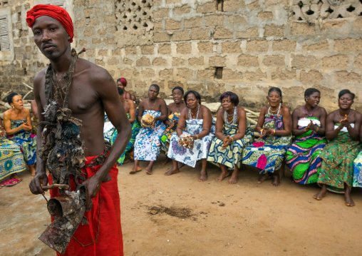 Benin, West Africa, Bopa, voodoo adept with a red scarf in front of a row of women during a ceremony