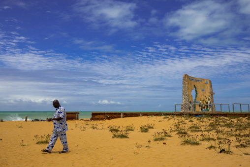 Benin, West Africa, Ouidah, man passing in front of the memorial of the grand jubilee of 2000
