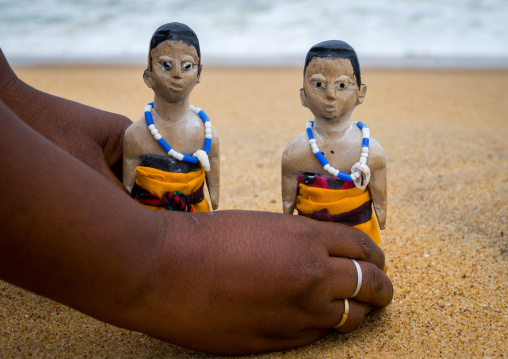 Benin, West Africa, Ouidah, mrs kpsouayo carrying the carved wooden figures made to house the soul of her dead twins on the beach