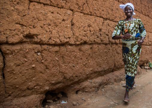 Benin, West Africa, Savalou, woman walking quickly along an adobe wall