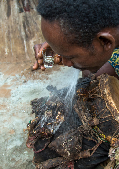 Benin, West Africa, Bopa, drummer spitting alcohol on a drum to wake up its spirit before a voodoo ceremony