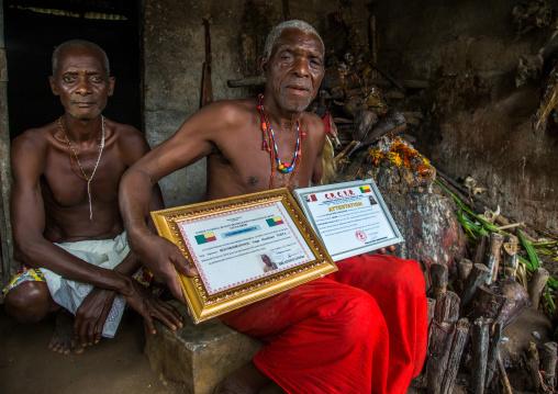 Benin, West Africa, Bopa, dah tofa voodoo master showing his diplomas in his temple