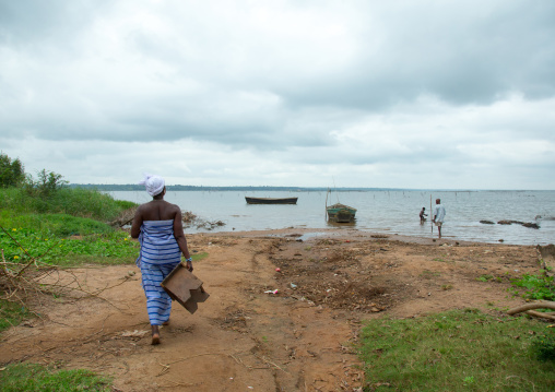 Benin, West Africa, Bopa, miss hounyoga going to bath the carved wooden figures made to house the soul of her dead twins in the lake
