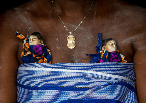 Benin, West Africa, Bopa, miss hounyoga carrying the carved wooden figures made to house the soul of her dead twins