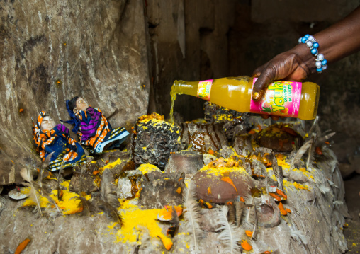 Benin, West Africa, Bopa, miss hounyoga putting fruit juice offerings to the deity dan for the voodoo dead twins cult
