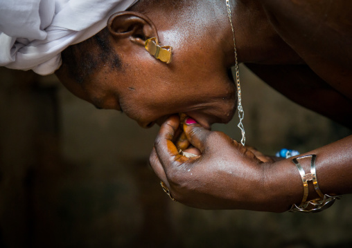 Benin, West Africa, Bopa, mrs hounyoga cuts a cola nut to make offerings to the twins spirits in the temple