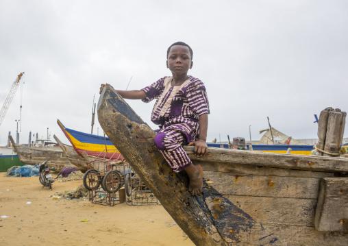 Benin, West Africa, Cotonou, boy sit on a fishermen boat in the port