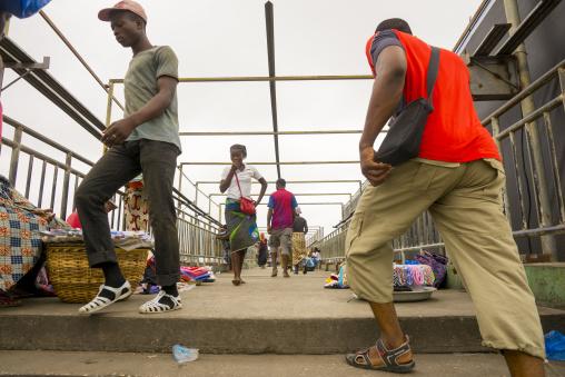 Benin, West Africa, Cotonou, people crossing the bridge over dantokpa market