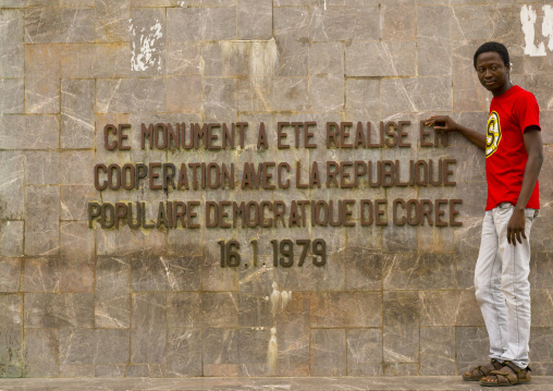 Benin, West Africa, Cotonou, beninese man pausing in front of 1977 martyrs monument made by north korean artists