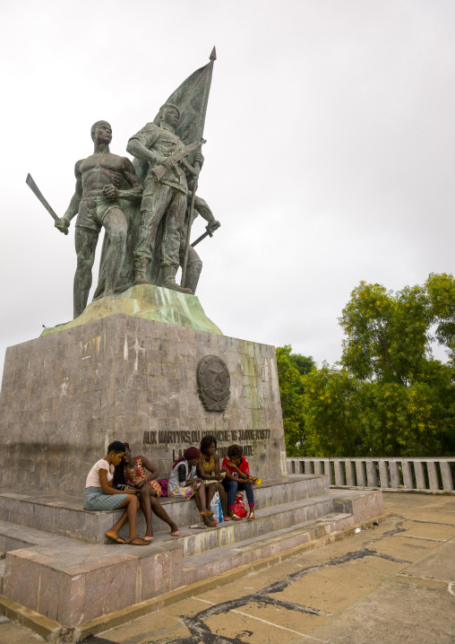Benin, West Africa, Cotonou, group of girls sitting in front of 1977 martyrs monument made by north korean artists