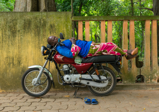 Benin, West Africa, Porto-Novo, man sleeping on top of motor bike