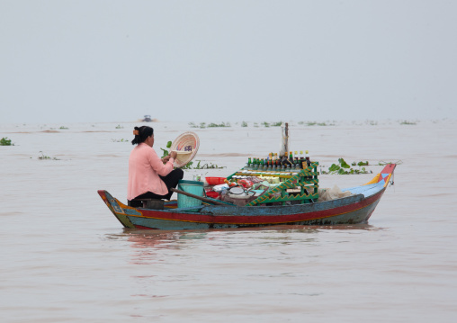 Woman selling food on boat in the floating village on Tonle Sap lake, Siem Reap Province, Chong Kneas, Cambodia