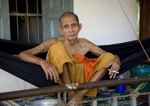 Tatooed monk on a hammock in a monastery, Battambang province, Battambang, Cambodia
