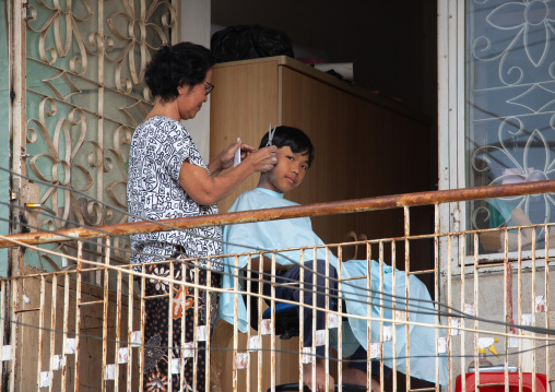 A boy having his hair cut by his mother on a balcony, Phnom Penh province, Phnom Penh, Cambodia