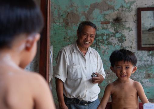 A boy having his hair cut by a man in a salon, Phnom Penh province, Phnom Penh, Cambodia