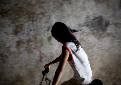 Portrait of a cambodian girl riding a bicycle, Phnom Penh province, Phnom Penh, Cambodia