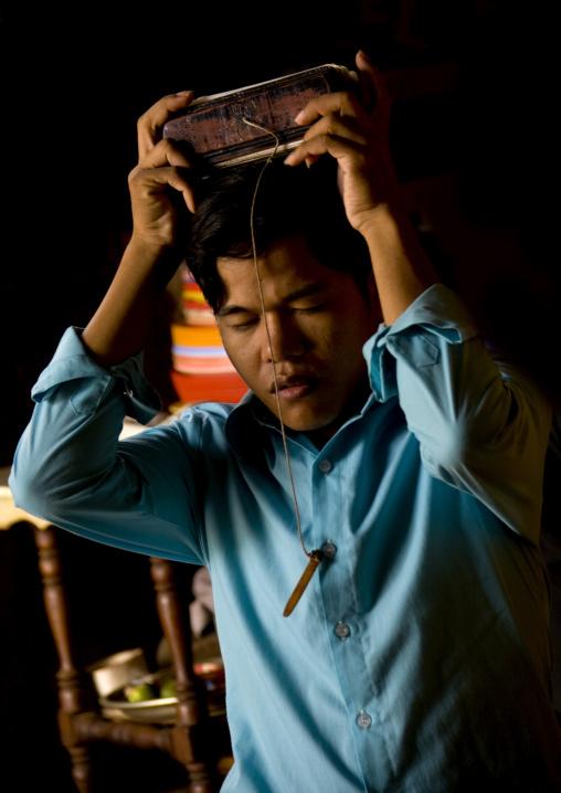 Cambodian man praying in a temple, Phnom Penh province, Phnom Penh, Cambodia