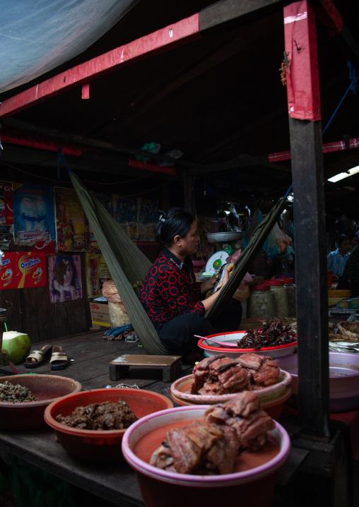 Cambodian woman on a hammock selling pork meat in a market, Phnom Penh province, Phnom Penh, Cambodia