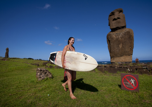 Surfer Passing  In Front Of Ahu Tautira In Hanga Roa, Easter Island, Chile