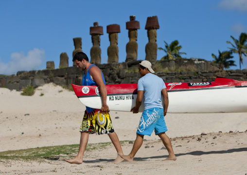 Men Carrying A Pirogue In Front Of Ahu Nau Nau At Anakena Beach, Easter Island, Chile