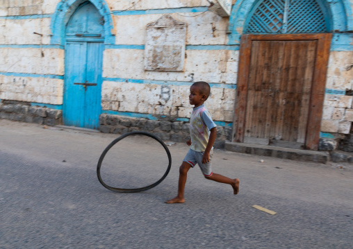 Boy playing in the street in front of an ottoman architecture house, Northern Red Sea, Massawa, Eritrea