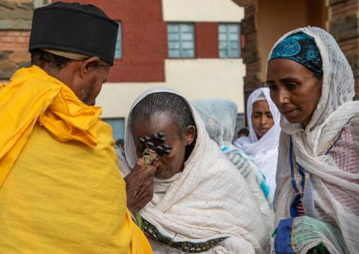 Eritrean women kissing the cross of a priest in enda mariam orthodox cathedral, Central region, Asmara, Eritrea