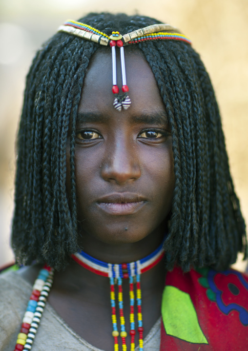 Portrait Of A Shy Karrayyu Tribe Girl With Stranded Hair And Colourful Jewels, Gadaaa Ceremony, Metehara, Ethiopia