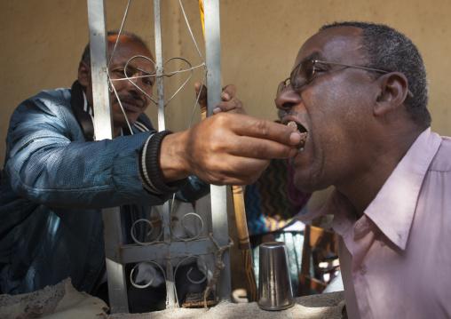 Man Feeding A Friend As A Friendship Gesture In Harar, Ethiopia