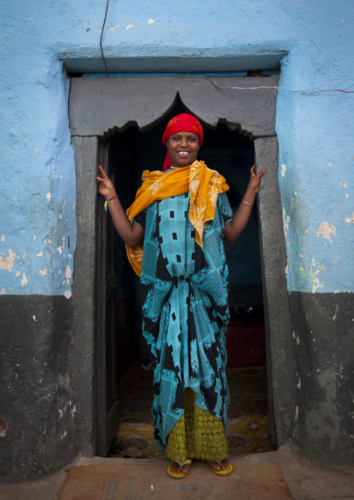 Portrait Of A Woman With Toothy Smile At The Entrance Of Her Blue-painted House, Harar, Ethiopia