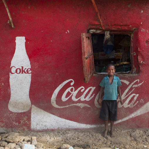 Smiling Kid Standing In Front Of A Wall Painted With A Coca Cola Advertisement, Dire Dawa, Ethiopia