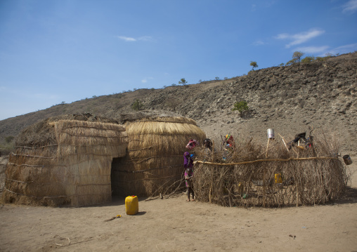 Karrayu Tribe Mother And Her Two Kids Behind The Wooden Fence Of Their House Down A Rocky Hill, Metahara, Ethiopia