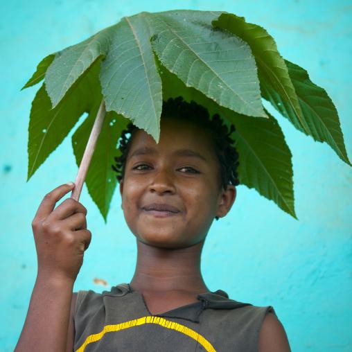 Young ara boy portrait with leaf made umbrella omo valley Ethiopia