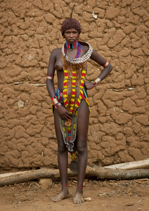 Hamer Beautiful Traditionally Dressed Hamer Tribe Woman Posing In Front Of Clay House Omo Valley Ethiopia
