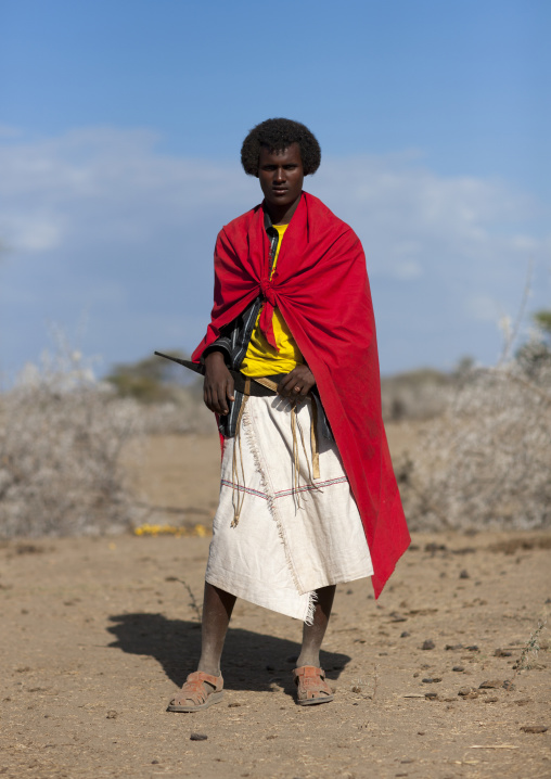 Portrait Of A Karrayyu Tribe Man In Red Clothes With Traditional Gunfura Hairstyle During Gadaaa Ceremony, Metahara, Ethiopia