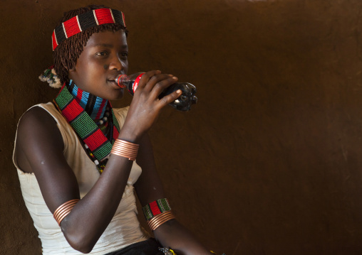 Hamer Tribe Woman In Traditional Outfit Drinking A Coca Cola, Turmi, Omo Valley, Ethiopia