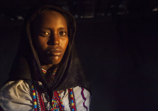 Karrayyu Tribe Woman Inside Her House Lighten By A Ray Of Light, Metahara, Ethiopia