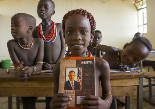 Hamer Tribe Girl Holding A Book With Barack Obama On The Cover In A School, Turmi, Omo Valley, Ethiopia