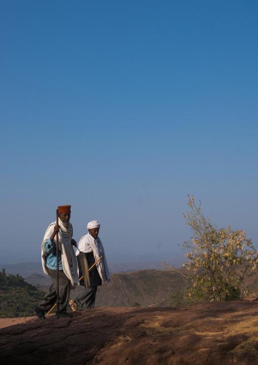 Ethiopian priests walking along a hill, Amhara region, Lalibela, Ethiopia