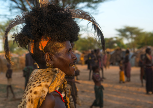 Dassanech man with leopard skin and ostrich feather headwears during dimi ceremony to celebrate circumcision of teenagers, Omo valley, Omorate, Ethiopia