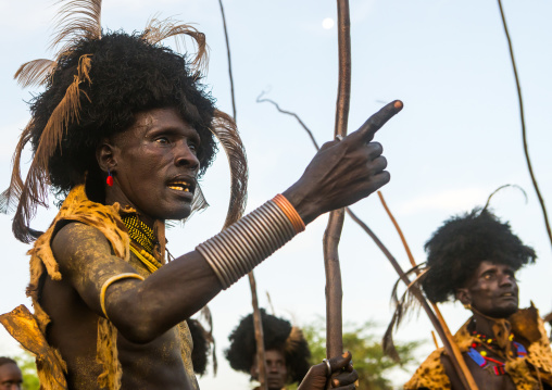 Dassanech men with leopard skins and ostrich feathers headwears during dimi ceremony to celebrate circumcision of teenagers, Omo valley, Omorate, Ethiopia